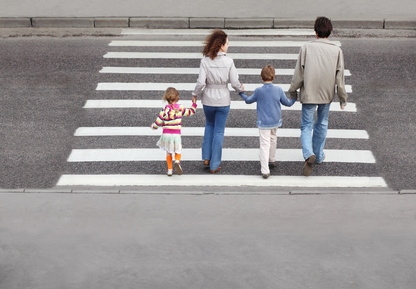 mother and father holds hand of children and crossing road