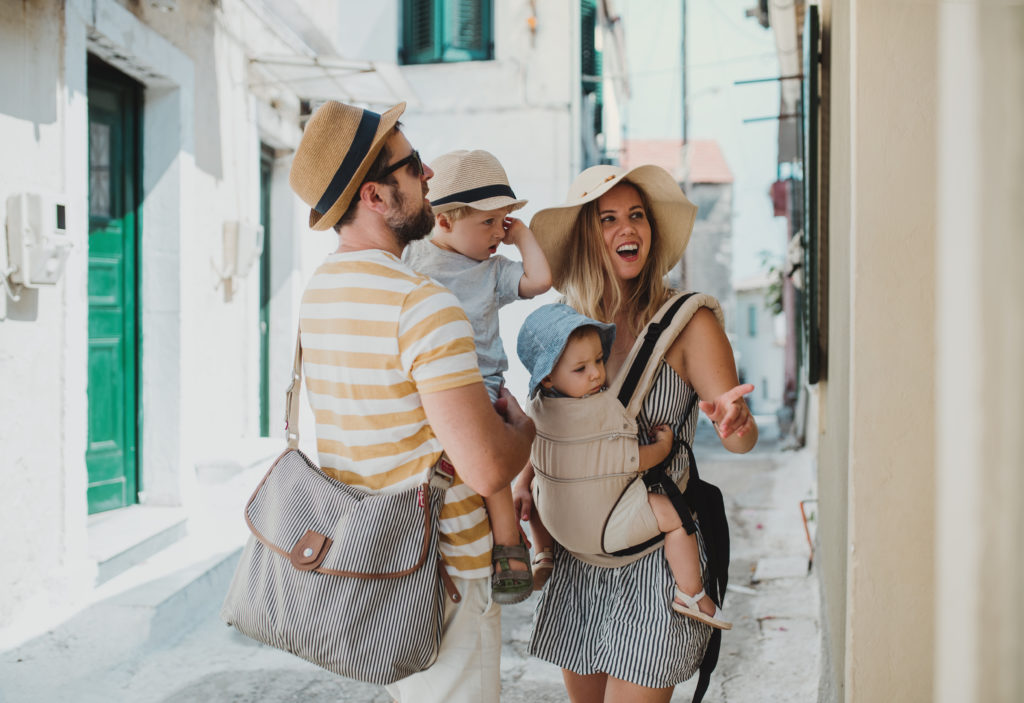 A young family with two toddler children walking in town on summer holiday.
